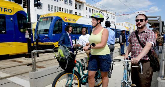 people on bikes and walking on light rail platform