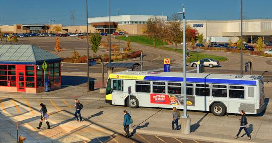 Bus arriving at transit center with pedestrians